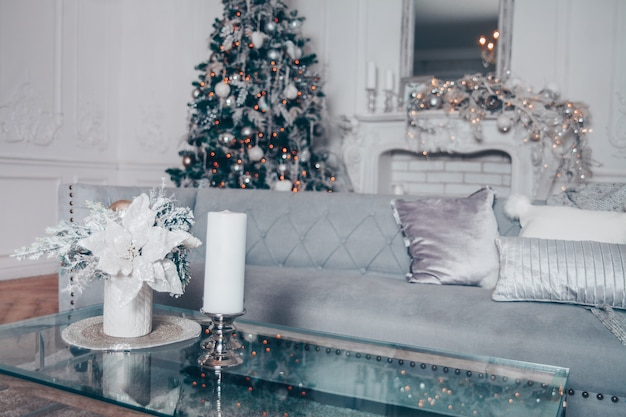 Klassiek wit kerstmisbinnenland met moderne elementen en verfraaide nieuwjaarboom.