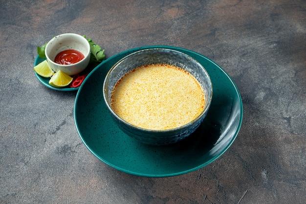 Klassieke aziatische pittige soep tom yum met garnalen, limoen en peterselie in een kom op een donkere achtergrond