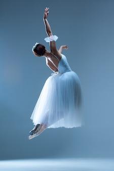 Klassieke ballerina die op blauw danst