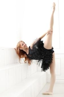 Klassieke ballerina vrouw in zwarte jurk oefenen voor de zwarte zwaan