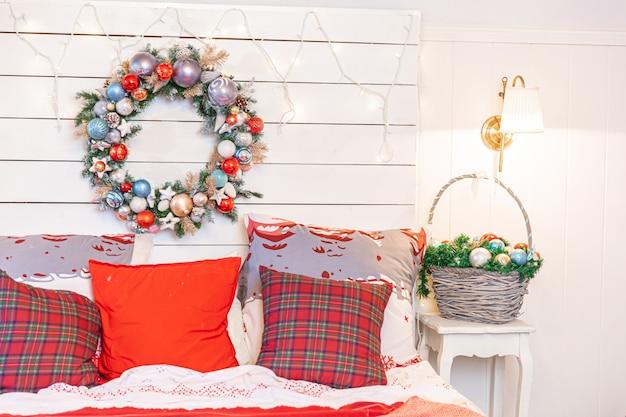 Klassieke binnenkamer met kerstboom en traditionele witrode versieringen. moderne schone witte klassieke stijl interieur appartement slaapkamer. kerstavond thuis. minimalistisch huisontwerp.