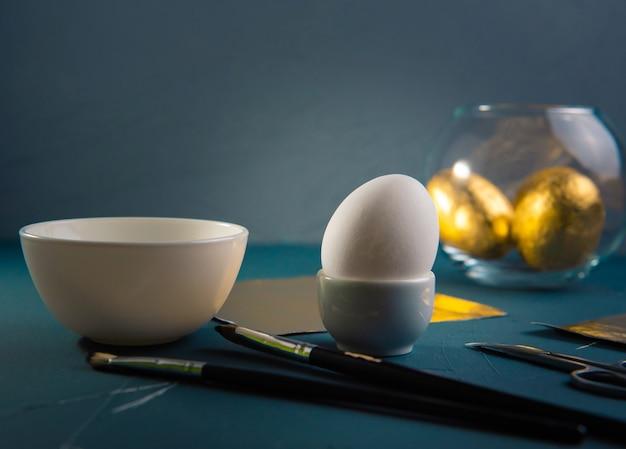 Klassieke blauwe tafel met ingrediënten voor het vergulden van paaseieren