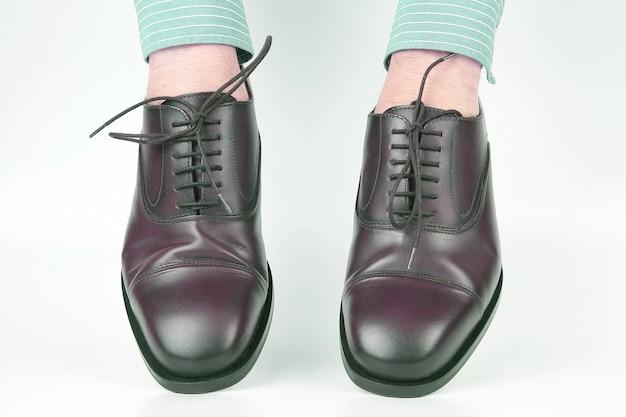 Klassieke bruine schoenen gedragen op de handen op een witte achtergrond. leer modieuze schoenen voor heren