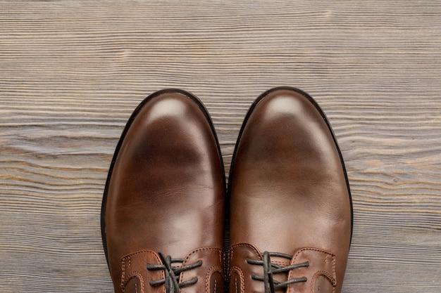 Klassieke bruine schoenen van modieuze mannen op een houten