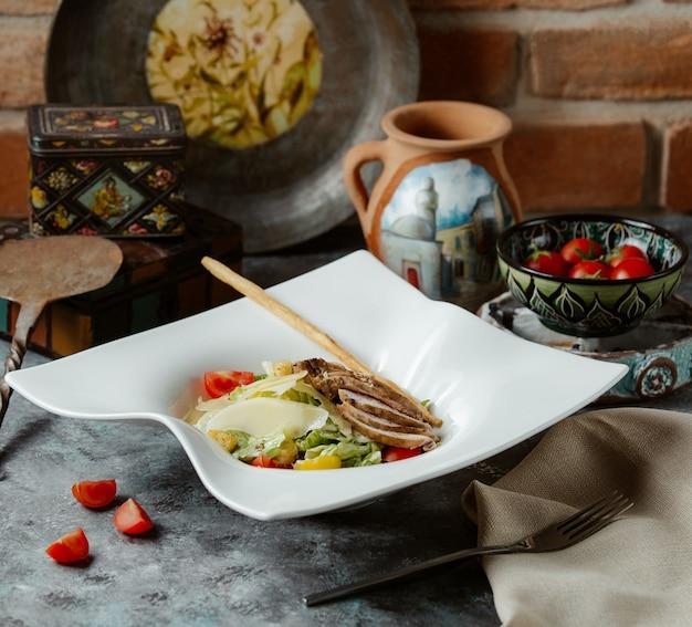 Klassieke caesarsalade gemaakt van gegrilde kipfilet, kersen en verse parmezaanse kaas