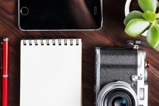 Klassieke camera met lege kladblok-pagina en rode pen op donkerbruine houten tafel, vintage tafel met telefoon en groene bloem