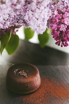 Klassieke chocolade fondant op een donkere ondergrond met bloemen