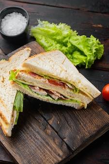Klassieke club sandwich met vlees, op donkere houten achtergrond