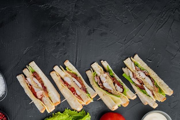 Klassieke clubsandwich met vlees, op zwarte achtergrond, bovenaanzicht met kopieerruimte voor tekst