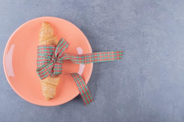 Klassieke croissant op oranje plaat over grijze achtergrond.