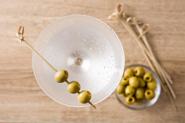 Klassieke droge drank met olijven op houten tafelblad bekijken