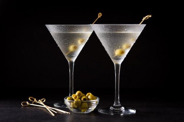 Klassieke droge martini met olijven op zwart