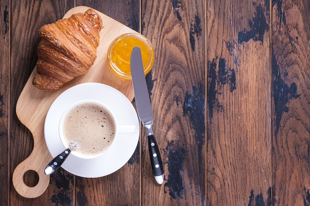 Klassieke franse ontbijtcroissant en sinaasappeljam