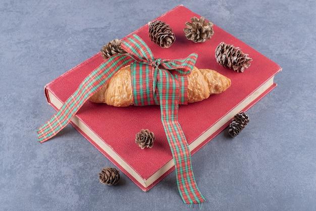 Klassieke franse verse croissant op rood boek.