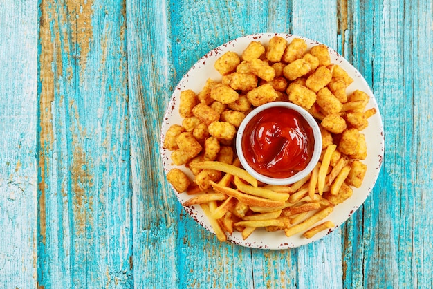 Klassieke frietjes en tasti taters met ketchup op houten tafel.