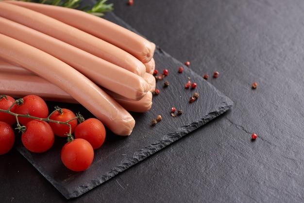 Klassieke gekookte vleesvarkensworstjes op snijplank met peper en basilicum en kerstomaatjes.