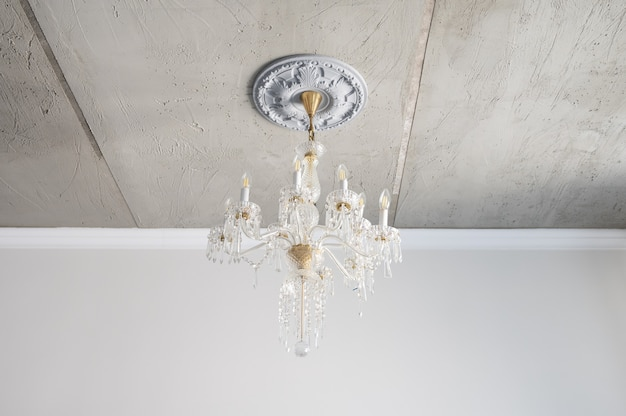 Klassieke glazen kroonluchter in wit geel, met geklede energiebesparende lampen.