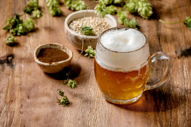 Klassieke glazen mok van vers koud schuimend lagerbier met groene hopbellen, tarwekorrel en rode gefermenteerde mout in keramische kommen achter over houten tafel. kopieer ruimte