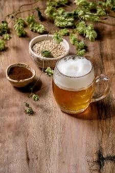 Klassieke glazen mok van vers koud schuimend lagerbier met groene hopbellen, tarwekorrel en rode gefermenteerde mout in keramische kommen achter over houten tafel.