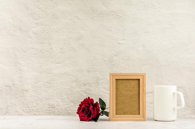 Klassieke houten fotolijst en rode roos met een witte koffiekop.