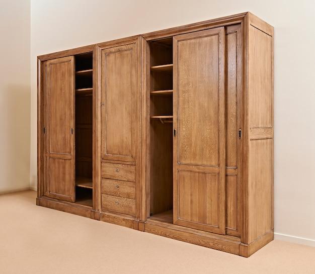 Klassieke houten kledingkast geopend tegen getextureerde muur