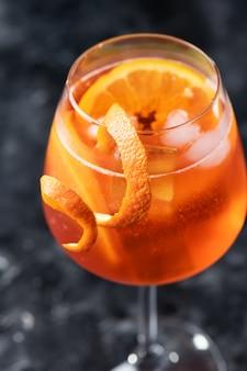 Klassieke italiaanse aperol spritz cocktail in glas op een donkere, close-up