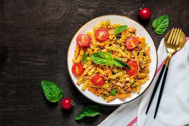 Klassieke italiaanse pasta in tomatensaus in witte kom op donkere houten tafel
