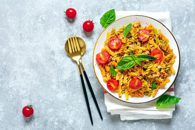 Klassieke italiaanse pasta in tomatensaus in witte kom op grijze betonnen tafel
