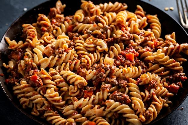 Klassieke italiaanse pasta met gehakt en groenten gekookt en geserveerd op pan. detailopname.