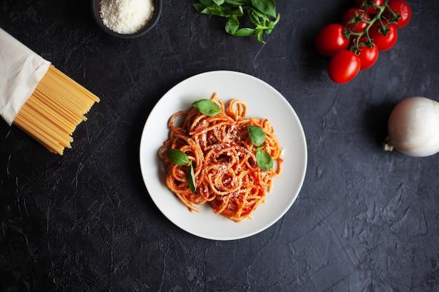 Klassieke italiaanse pasta met tomatensaus, parmezaanse kaas en basilicum op plaat