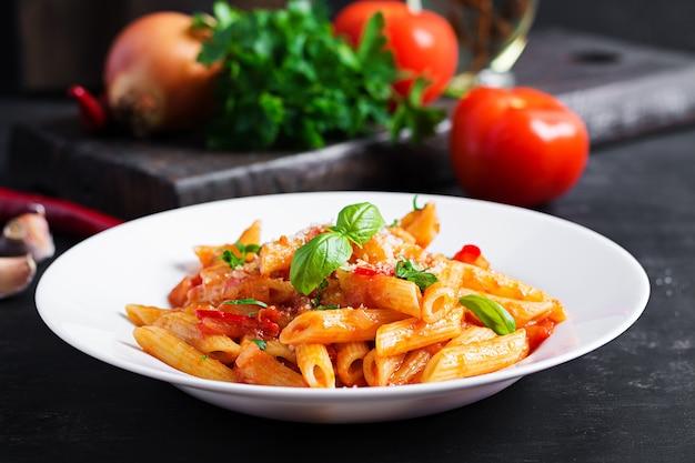 Klassieke italiaanse pasta penne alla arrabiata met basilicum en vers geraspte parmezaanse kaas op donkere tafel. penne pasta met chilisaus arrabbiata.
