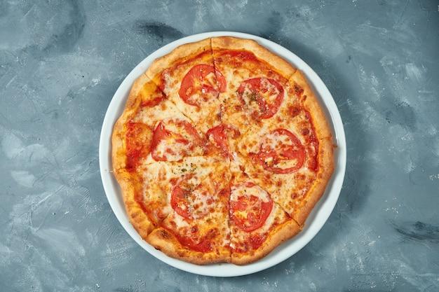 Klassieke italiaanse pizza margarita met tomaten en kaas in een witte plaat op een betonnen ondergrond