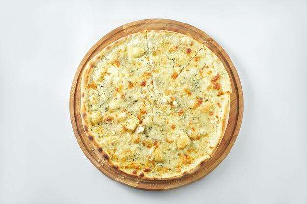 Klassieke italiaanse pizza met 4 soorten kaas op een houten dienblad op een witte plaat