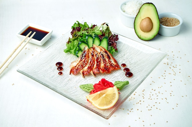 Klassieke japanse sashimi - rauwe paling met salade op een witte plaat in een compositie met ingrediënten