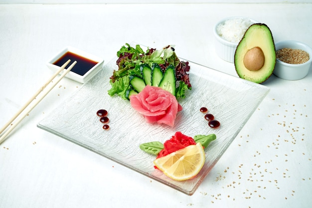 Klassieke japanse sashimi - tonijn met salade op een witte plaat in een compositie met ingrediënten