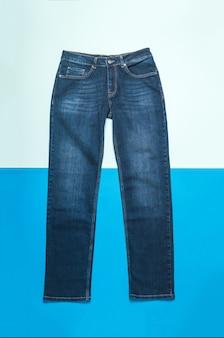 Klassieke jeans op een licht- en donkerblauwe ondergrond. jeans en denimkleding.