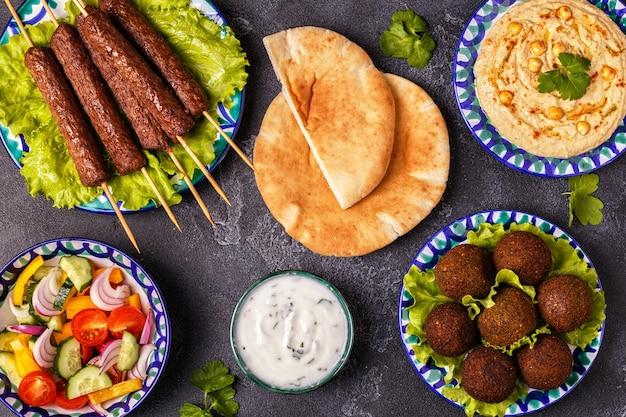 Klassieke kebab, falafel en hummus op de borden. bovenaanzicht.