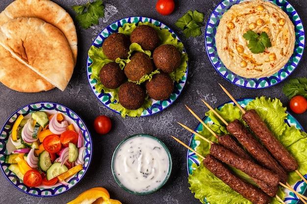 Klassieke kebabs, falafel en hummus op de borden. bovenaanzicht.