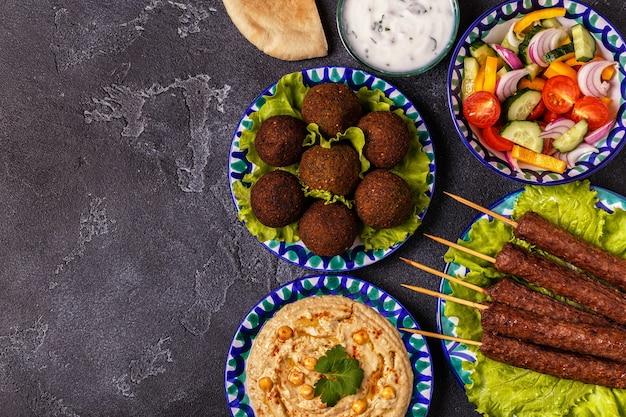 Klassieke kebabs, falafel en hummus op de borden.