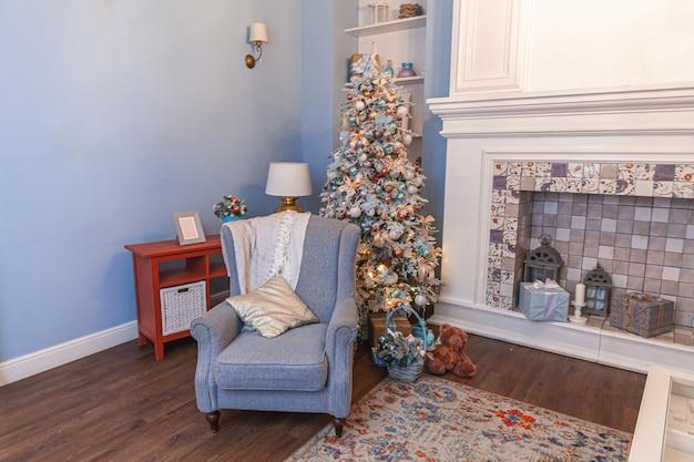 Klassieke kerst ingerichte binnenkamer, nieuwjaarsboom met zilveren versieringen. moderne blauwe klassieke stijl interieur appartement met open haard en fauteuil. kerstavond thuis.