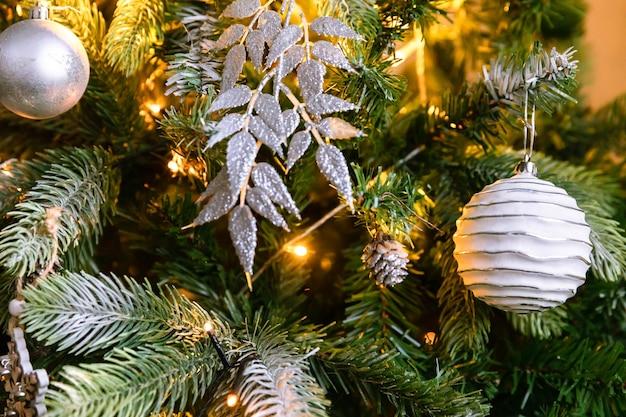Klassieke kerst versierde nieuwjaarsboom. kerstboom met witte en zilveren versieringen, ornamenten speelgoed en bal. modern klassiek interieur appartement. kerstavond thuis.
