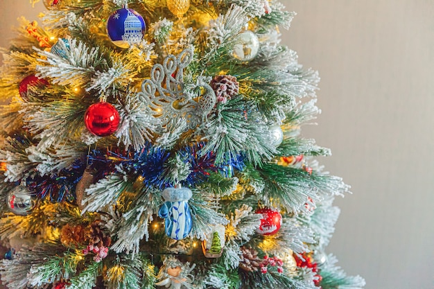 Klassieke kerst versierde nieuwjaarsboom met rood blauw en wit ornament speelgoed en bal op grijze muur achtergrond. modern klassiek interieur appartement. kerstavond thuis. ruimte kopiëren.