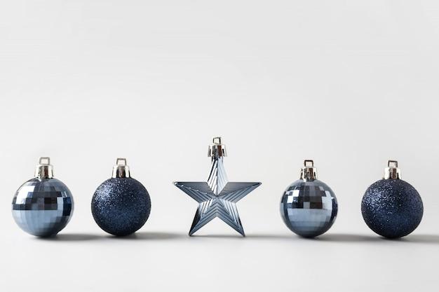Klassieke kerstballen en ster in rij op neutraal pastel grijs