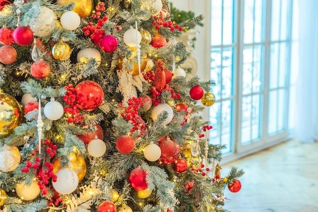 Klassieke kerstmis nieuwjaar versierde nieuwjaarsboom met rood goud en wit ornamentversieringen speelgoed en bal. modern klassiek interieur appartement. kerstavond thuis.