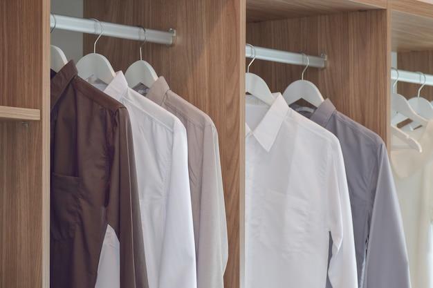 Klassieke kleurenoverhemden die in houten garderobe hangen