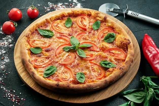 Klassieke margarita pizza met mozzarella, tomaten en basilicum op een houten bord. italiaanse pizza in een compositie met ingrediënten op een zwarte tafel