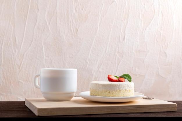 Klassieke new york cheesecake met aardbeien en kopje koffie of thee.