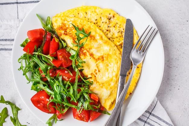 Klassieke omelet met kaas en tomatensalade op witte plaat, hoogste mening.
