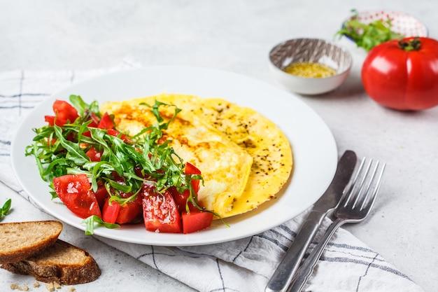 Klassieke omelet met kaas en tomatensalade op witte plaat.