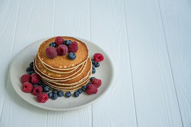 Klassieke pannenkoeken met verse bessen op een blauwe houten tafel. pannenkoeken met fruit.